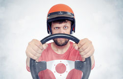 Bearded male in red helmet with steering wheel. car driver concept Stock Photo
