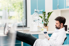 Bearded male scientist holding flask with reagent while sitting in chemical lab. Side view of bearded male scientist holding flask with reagent while sitting in Royalty Free Stock Photo