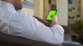 Bearded male sitting on sofa and scrolling on cellphone with green screen, app. Stock footage stock footage
