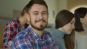 Bearded male student turns his face. Bearded male student turning his face to the camera at the lecture hall. Close up of young handsome undergraduate sitting Royalty Free Stock Photos