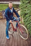 A bearded male with a stylish haircut dressed in casual clothes with a backpack, sitting on a retro bicycle in a city. Bearded male with a stylish haircut royalty free stock photography