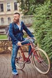 A bearded male with a stylish haircut dressed in casual clothes with a backpack, sitting on a retro bicycle in a city. Bearded male with a stylish haircut royalty free stock photo