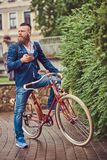 A bearded male with a stylish haircut dressed in casual clothes with a backpack, sitting on a retro bicycle in a city. Bearded male with a stylish haircut stock images