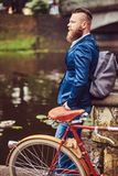 Bearded male with a stylish haircut dressed in casual clothes with a backpack, standing with a retro bicycle near the stock photo