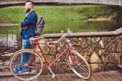 Bearded male with a stylish haircut dressed in casual clothes with a backpack, standing with a retro bicycle near the. A bearded male with a stylish haircut royalty free stock images