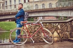 Bearded male with a stylish haircut dressed in casual clothes with a backpack, standing with a retro bicycle near the. A bearded male with a stylish haircut stock images