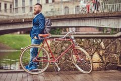 Bearded male with a stylish haircut dressed in casual clothes with a backpack, standing with a retro bicycle near the. A bearded male with a stylish haircut stock photos