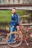 Bearded male with a stylish haircut dressed in casual clothes with a backpack, standing with a retro bicycle near the. A bearded male with a stylish haircut royalty free stock image