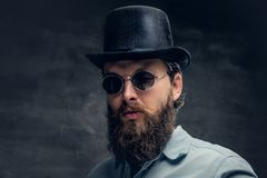Bearded male in sunglasses and cylinder hat. Portrait of serious, bearded male in sunglasses and cylinder hat Stock Images