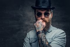 Bearded male in sunglasses and cylinder hat. Portrait of serious, bearded male in sunglasses and cylinder hat Royalty Free Stock Images