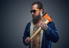 Bearded male in sunglasses holds axe. Portrait of bearded male in sunglasses with a tattoo on his chest wearing a denim jacket and holds axe over grey Royalty Free Stock Photos