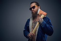 Bearded male in sunglasses holds axe. Portrait of bearded male in sunglasses with a tattoo on his chest wearing a denim jacket and holds axe over grey Stock Images