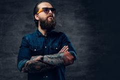 Bearded male in sunglasses with tattooed crossed arms. Portrait of bearded male in sunglasses with tattooed crossed arms Stock Photo