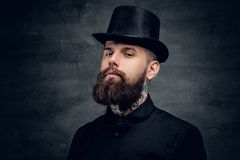 Bearded male with tattoo on his neck and top hat cylinder on hea. D Royalty Free Stock Images