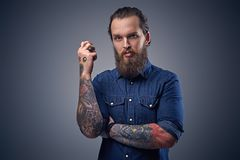 Bearded male with tattoos on arms. Bearded male with tattoos on arms, dressed in denim shirt over grey background Royalty Free Stock Photos