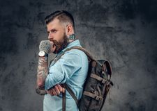 Bearded male with tattoos on his arms holds urban backpack. Bearded male with tattoos on his arms, dressed in a denim shirt holds urban backpack Royalty Free Stock Images