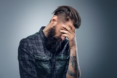 Bearded male with tattoos on his arms. Portrait of bearded male with tattoos on his arms, dressed in a plaid flannel shirt over grey vignette background Royalty Free Stock Photos