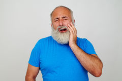Bearded male touching his cheek as if suffering from toothache. Bearded male in blue T-shirt is touching his cheek as if suffering from toothache isolated Stock Photo