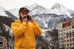 Bearded male tourist in yellow hoodie and cap stands on background of high snowy mountains, talking on mobile phone. Lifestyle royalty free stock image