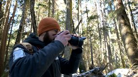 A bearded male traveler photographer with his camera in the winter forest takes pictures of nature. Travel concept for stock video