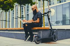 Bearded male using a laptop after electric scooter ride. Shaved head tattooed, bearded male using a laptop over modern building background after the electric Stock Photo