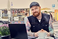 Bearded male using laptop in a summer street cafe. Bearded tattooed male dressed in a waistcoat and tweed cap using laptop in a summer street cafe Royalty Free Stock Photos