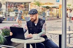 Bearded male using laptop in a summer street cafe. Bearded tattooed male dressed in a waistcoat and tweed cap using laptop in a summer street cafe Stock Photography