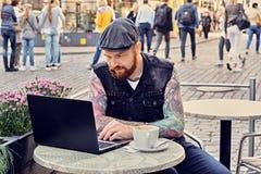 Bearded male using laptop in a summer street cafe. Bearded tattooed male dressed in a waistcoat and tweed cap using laptop in a summer street cafe Royalty Free Stock Image