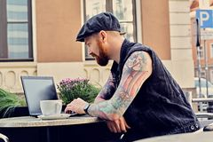 Bearded male using laptop in a summer street cafe. Bearded tattooed male dressed in a waistcoat and tweed cap using laptop in a summer street cafe Stock Images