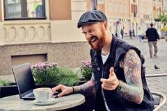 Bearded male using laptop in a summer street cafe. Bearded tattooed male dressed in a waistcoat and tweed cap using laptop in a summer street cafe Stock Photos