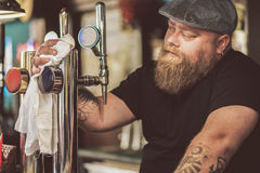 Bearded male working as bartender in pub Stock Photo