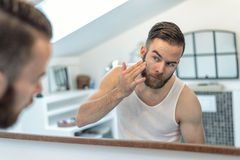 Bearded man applying a face mask Stock Photos