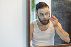 Bearded man applying a face mask Stock Photos