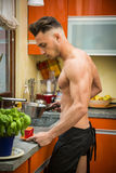 Bearded man in apron preparing breakfast. Side view of sexy muscular topless man in black apron making coffee for breakfast in kitchen Royalty Free Stock Photos