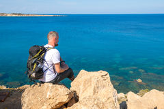 Bearded man with backpack sits on the rocky shore. And  looking at the sea. Sunny day on Cape Greco, Cyprus. Back view Stock Image