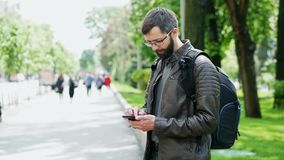 Bearded man with bag uses mobile phone on the street stock footage