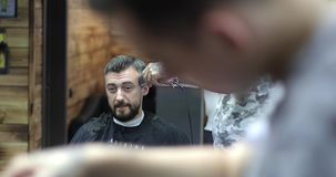 A bearded man in a barbershop. Hairdresser does a man`s haircut. View through reflection in the mirror. 4K stock footage
