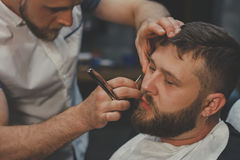 Bearded Man In Barbershop. Serious Bearded Man Getting Beard Haircut With A Straight Razor By Barber While Sitting In Chair At Barbershop. Barbershop Theme royalty free stock photos