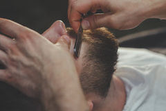 Bearded Man In Barbershop. Serious Bearded Man Getting Beard Haircut With A Straight Razor By Barber. Barbershop Theme royalty free stock image