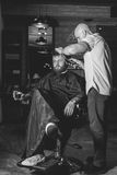 Bearded Man In Barbershop. Serious Bearded Man Getting Haircut By Barber And Holding A Glass Of Whiskey While Sitting In Chair At Barbershop. Barbershop Theme royalty free stock photos