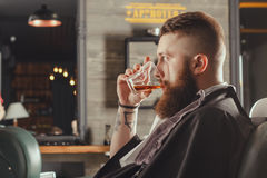 Bearded Man In Barbershop. Serious Young Bearded Man Sitting In Chair At Barbershop And Drinking Whiskey From A Glass . Barbershop Theme royalty free stock image