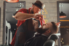 Bearded Man In Barbershop. Young Bearded Man Getting Beard Haircut With A Straight Razor By Barber. Barbershop Theme Royalty Free Stock Photos