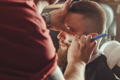 Bearded Man In Barbershop. Young Bearded Man Getting Beard Haircut With A Straight Razor By Barber. Barbershop Theme Stock Image