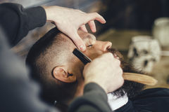 Bearded Man In Barbershop. Young Bearded Man Getting Beard Haircut With A Straight Razor By Barber. Barbershop Theme Stock Images