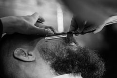 Bearded Man In Barbershop. Young Bearded Man Getting Beard Haircut With A Straight Razor By Barber. Barbershop Theme Stock Photos