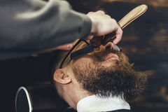 Bearded Man In Barbershop. Young Bearded Man Getting Beard Haircut With A Straight Razor By Barber. Barbershop Theme Royalty Free Stock Image