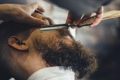 Bearded Man In Barbershop. Young Bearded Man Getting Beard Haircut With A Vintage Straight Razor By Barber. Barbershop Theme Royalty Free Stock Photography