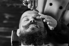 Bearded Man In Barbershop. Young Bearded Man Getting Haircut With A Straight Razor By Barber. Barbershop Theme Royalty Free Stock Photos