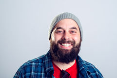 Bearded man with baseball cap is smiling. Young bearded man with woolen cap is smiling Royalty Free Stock Photo
