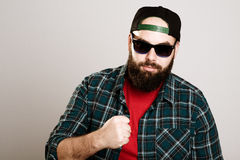 Bearded man with baseball cap and sunglasses is looking angry Stock Photography
